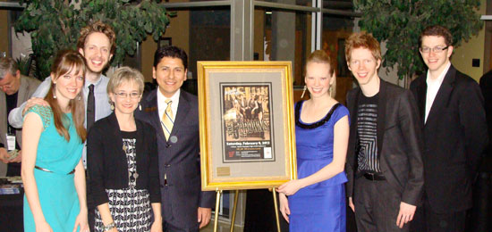 "J.R. Mooney Galleries supports Boerne Performing Arts by providing a professionally matted and framed poster featuring each of the visiting artists. Combining this visual arts presentation with the performing arts concert melds the entire arts community into promoting the cultural life in Boerne. In turn, autographed posters by the visiting artists are matted and framed by J.R. Mooney Galleries as a ""thank you gift"" to each of the specific concert sponsors. Picture above are (left to right) Melody Brown, Gregory Brown, Lori and Paul De Luna (J.R. Mooney Galleries), Deondra Brown, Ryan Brown and Stephen Beus, surrounding the artwork on display in the lobby at Champion High School."